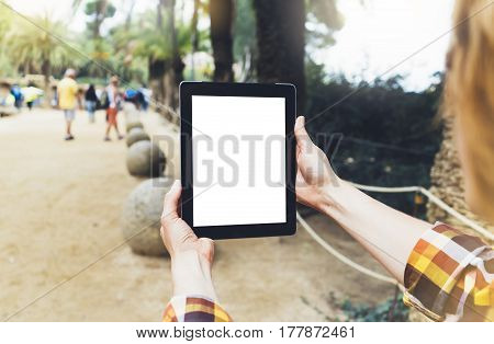 Hipster person holding in hands digital tablet with empty blank screen girl photograph on computer against a background nature park landscape mock up technology blur female hands tourist using gadget