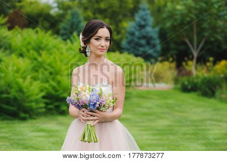Half-length portrait of a beautiful bride in park. Cute lady with a bouquet in pink wedding dress outdoors. Look at the camera. Grass trees and bushes in the background.
