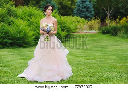 Portrait of a beautiful bride in park. Cute lady with a bouquet in pink wedding dress outdoors. Looking sideways. Grass trees and bushes in the background.