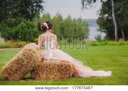 Portrait of a beautiful bride with a bouquet outdoors. Cute lady sits with her back on pressed straw briquettes. Hay bale stack. Pink wedding dress. Grass trees and bushes in the background.