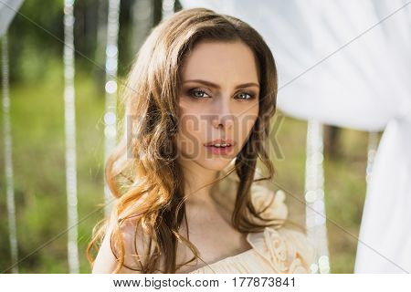 Beauty portrait of a very pretty young sensual girl. Doll appearance. Sensual woman with brown hair in a pink wedding dress on nature near the wedding arch. Long hair. Natural light. Sensual model