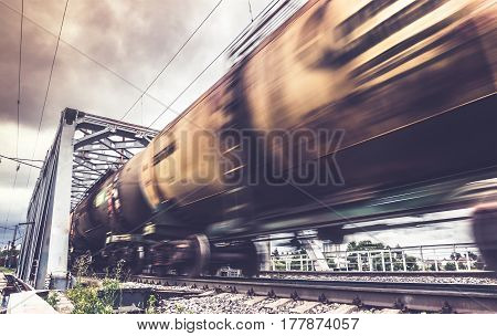 Freight train goes through the bridge , railway wagons with motion blur effect. Transportation, railroad, toned image