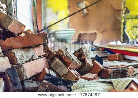 Destroyed homes, pile of bricks in the blurry background of ruined walls. Can be used as an illustration of military destruction or natural disaster, earthquake, copy space