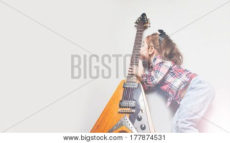 Beautiful artistic little girl playing guitar on grey background Place for your text