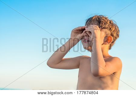 A boy pretends that looking through binoculars