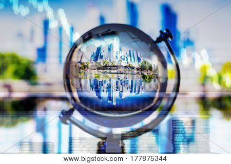 Money growing up with stock market graph background and small world with city scape reflection inside