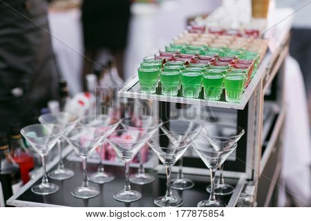 Variety of colorful green red and white beautiful alcohol sweet shooters shots cocktail fresh beverage in small glasses standing in row on mobile bar.