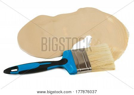 Spilled beige paint and brush isolated on white background. The concept of creativity.