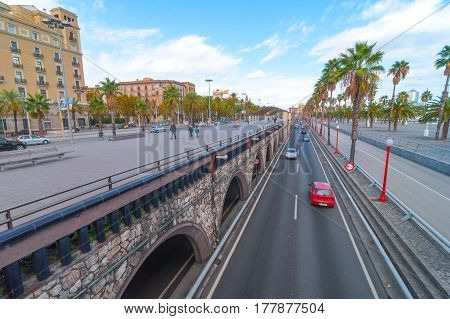 Barcelona, Spain, Nov 3rd, 2013:  Travel & Tourism.  Urban outdoors, people taking advantage of warm weather.  Walking on concourse over traffic filled tunnel. auto traffic along Palm tree lined road.