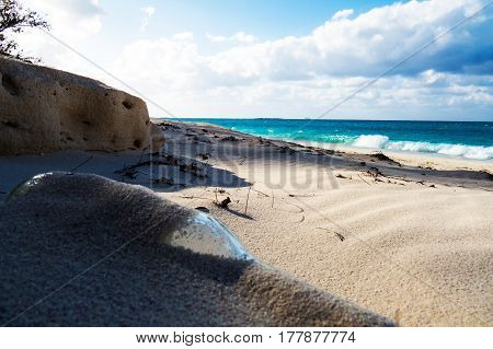 A glass bottle stuck in the sand on a sunny tropical beach New Providence, Nassau, Bahamas.