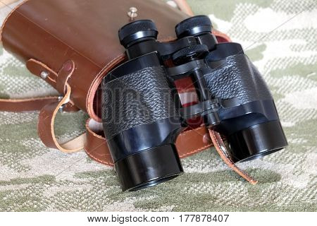 Vintage Porro prism black color military binoculars and brown leather carry case with strap on camouflage background side view close up