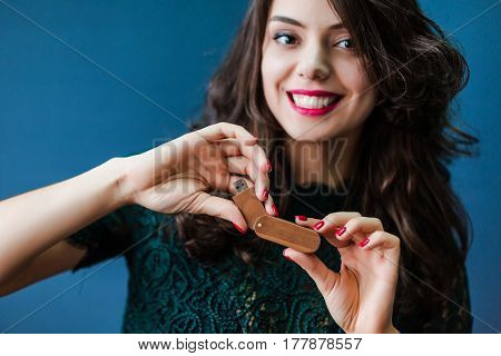 Young smiling woman holding wooden usb stick in hands