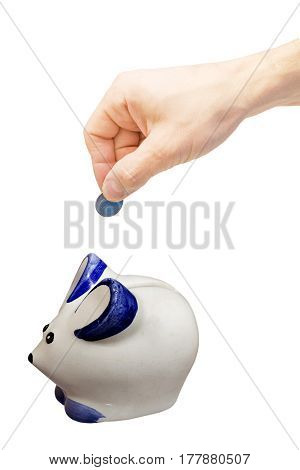 Hand with coin over a piggy bank on white background. clipping path.