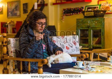 Eskisehir, Turkey - March 13, 2017: Girl Caressing A White Cat