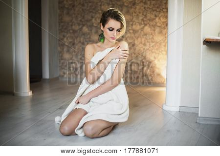 Sexy sweet girl with tanned skin and white hair with a white cloak sitting on the floor. Woman in white knitted poncho. Beautiful earrings of a peacock feather. Model in poncho