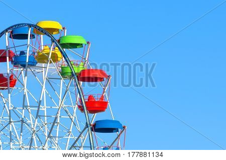 Wheel of amusement multi-colored cabin on the blue sky background.