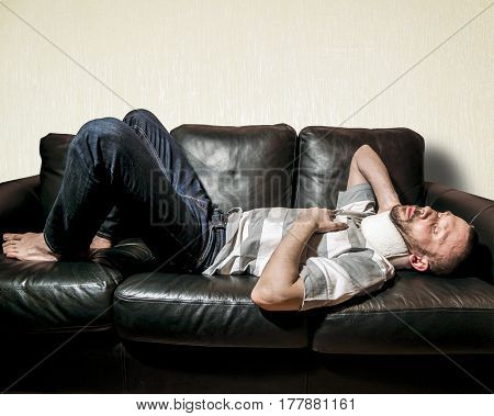 A man with a sore neck in the bus lies on the black sofa