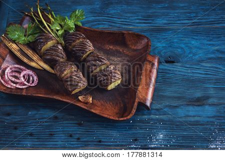 Grilled potato on a blue wooden background