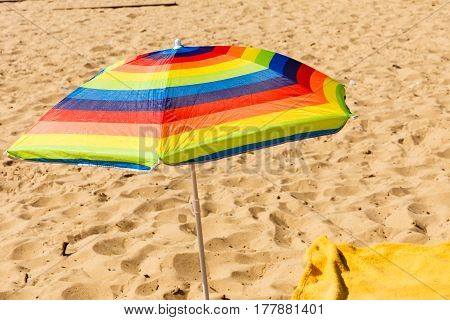Beach objects and accessories concept. Colorful summer umbrella parasol during summertime weather.