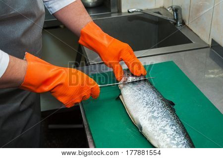 Chef cutting salmon fish with knife