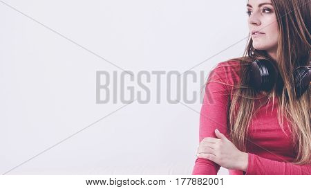 Young lady wearing headphones. Happy girl sitting on sofa. Music leisure relax fashion concept.