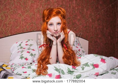 Woman with long red curly hair gathered into braids in nightgown in bed under a blanket. Red-haired girl with a pretty face pale skin blue eyes and bright unusual appearance in the bedroom in bed