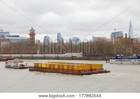 LONDON GREAT BRITAIN - FEB 27 2017: Towboat tow many yellow containers on the river Thames. February 27 2017 in London Great Britain
