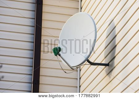 Satellite dish on the wall. Satellite television. Modern technologies. Satellite dish concept