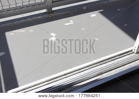 Small outside cement patio that has flaking gray paint that needs repair. Sunny gray cement deck paint that is weather-beaten chipping away and could be improved.