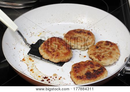 Four ground turkey meat burgers cooked in a non-stick pan on a stove top. A spatula lifting up one of four turkey burgers that were cooked in a frying pan.