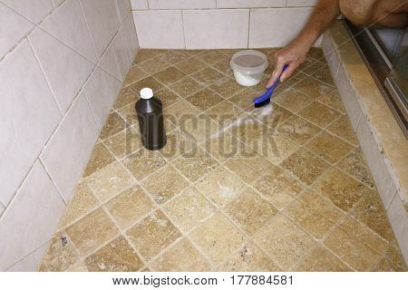 Adult male hand with a small blue and black brush cleaning floor grout in a shower. White male cleaning shower grout with hydrogen peroxide and baking soda.