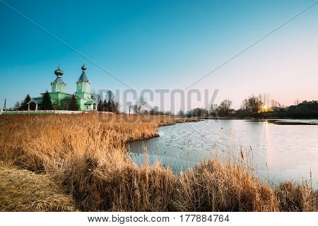 Old Wooden Orthodox Church Of The Holy Trinity In Village Old Krupets, Dobrush District, Gomel Region, Belarus. Landscape With Old Church And Spring Or Autumn Frozen River With Thickets of Bulrush At Evening.