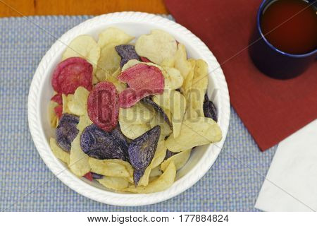 Three different colors of potato chips with tomato juice. Colorful red white and blue chips made from Crimson Purple Majesty and Chipeta or Atlantic potatoes.