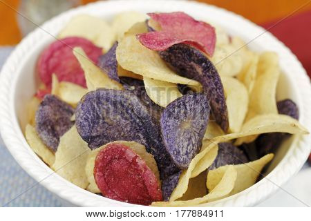 Red yellow and purple potato chips in a bowl close-up. Red white and blue theme food potato chips made from Crimson Purple Majesty and Chipeta or Atlantic potatoes