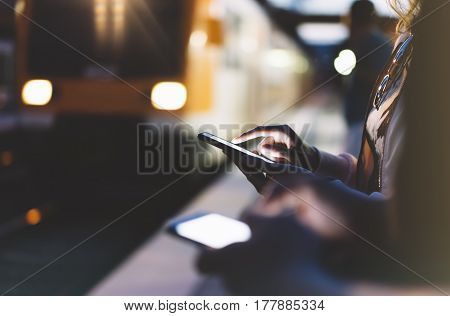Enjoying travel. Young woman waiting on station platform on background light electric moving train using smart phone in night. Tourist texting message and plan route of stop railway railroad transport