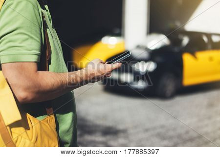 Man pointing finger on screen smartphone on background yellow taxi tourist hipster using in hands mobile phone person connect wifi internet and calls taxi headlights auto on backdrop city street mockup