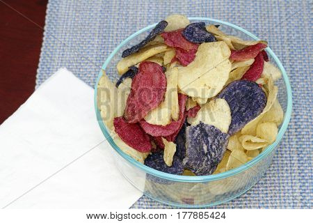 Crunchy appetizer of potato chips made from Crimson red Purple Majesty and Chipeta Atlantic potatoes. Potato chips in red white and blue in a glass bowl on a table.