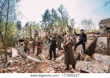Pribor, Belarus - April 24, 2016: Group Of Re-enactors Dressed As Russian Soviet Red Army Soldiers Of World War II Celebrate Victory And Salute From Weapons In Air On Background Of Ruined Building
