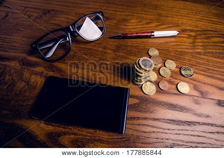 Concept of financial and economics. Smart phone, money, pen and glasses on a wooden table. Work in office. Investment.