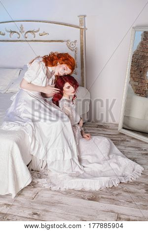 Two beautiful sensual girls with red hair in a beautiful white wedding Victorian dresses. Female style. The fragile girl. Thin waist. Two sensual women sitting in the bedroom on a white bed