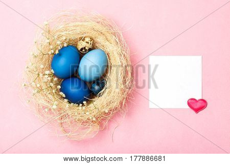 Easter eggs in blue colors in a nest on the pink background. The place for the text is decorated with heart. The concept of stylish decoration for Easter greeting cards etc. Flat lay
