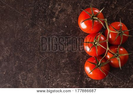 Ingredients for salad and diet. Red tomatoes lie on a dark marble table. Space for text and design. Flat lay copyspace. Diet concept.