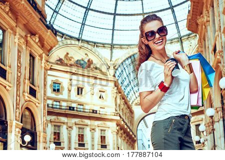 Smiling Fashion Woman With Shopping Bags And Coffee Cup