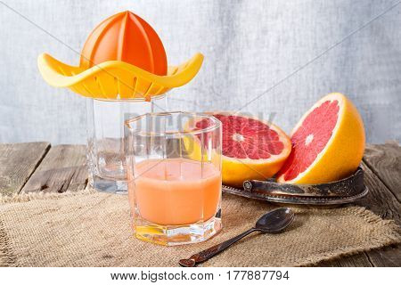 Freshly squeezed juice of grapefruit and its fruits. Juice in glasses on a grapefruit half background. The table is issued in rural style