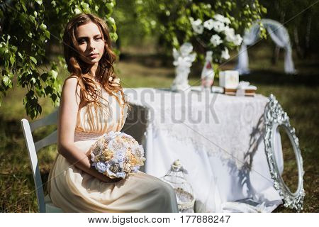 Beauty portrait of a very pretty young sitting girl. Doll appearance. Woman sitting on chair with brown hair in a pink wedding dress on nature near the wedding decor. Long hair. Natural light. Model posing in nature