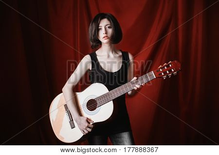 Play on guitar. Emotional portrait of brunette girl with short straight black hair with a natural make-up on a red background. A woman in a black T-shirt with a guitar in her hands