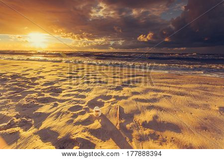 Polluted beach shore. Plastic disposable cup abandoned on sand beautiful golden sunset in the background. Earth ecology