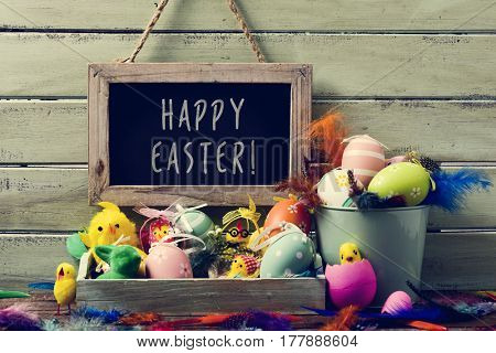 a wooden-framed chalkboard with the text happy easter hanging on a rustic wooden wall, and a pile of different decorated easter eggs, some teddy chickens and feathers of different colors