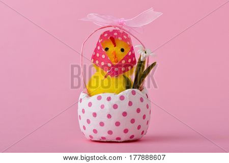 a funny lady teddy chick wearing a pink headscarf patterned with white dots emerging from a cracked white eggshell patterned with pink dots, against a pink background with a blank space around it
