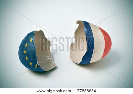 the two halves of a cracked eggshell, one patterned with the flag of the European Community and the other one patterned with the flag of France